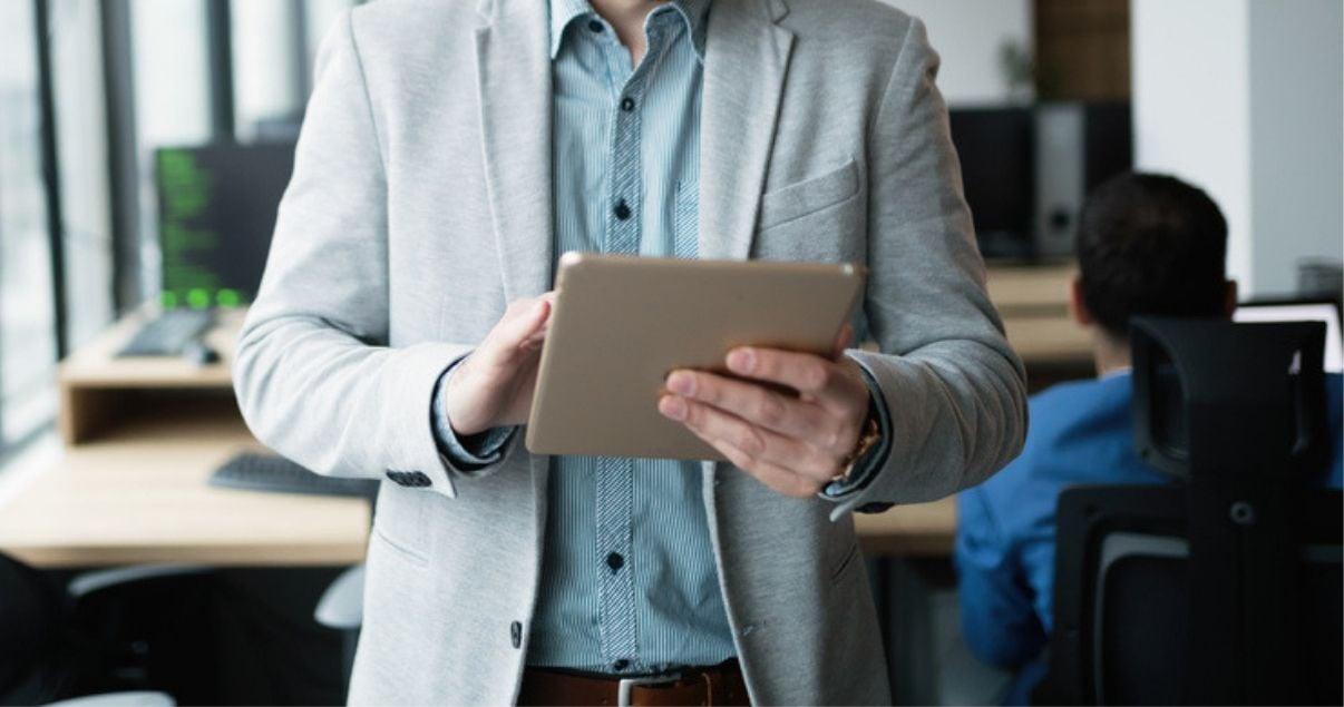 hombre de traje sosteniendo tablet mirando marketing de contenidos en ella