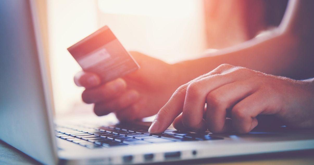 hombre mirando marketing de contenido en computadora y comprando online con tarjeta de crédito